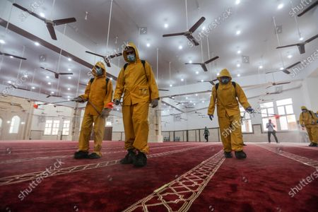Palestinian workers disinfect a Mosque, as a preventive measure amid the coronavirus disease (COVID-19) outbreak, after the holy places reopen to worshippers to perform the weekly Islamic ritual, in Khan Younis in the southern of Gaza strip, on October, 9, 2020.