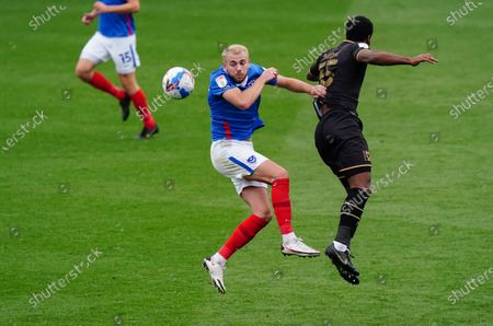 Jack Whatmough of Portsmouth and Cameron Jerome of MK Dons collide for a header