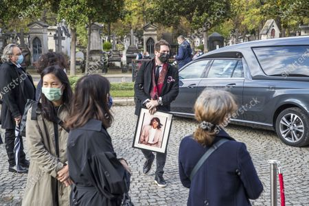 A relative holds a portrait of late Japanese fashion designer Kenzo Takada as he arrives to a ceremony at a funeral chapel of the Pere Lachaise cemetery in Paris, France, 09 October 2020. Takada has died in a hospital in France on 04 October 2020 after suffering from Covid-19. He was 81.
