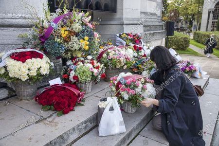 People lay flowers to pay their respects to late Japanese fashion designer Kenzo Takada at a funeral chapel of the Pere Lachaise cemetery in Paris, France, 09 October 2020. Takada has died in a hospital in France on 04 October 2020 after suffering from Covid-19. He was 81.