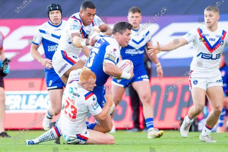 St Helens's Louie McCarthy-Scarsbrook is tackled by Wakefield's Josh Wood & Reece Lyne.