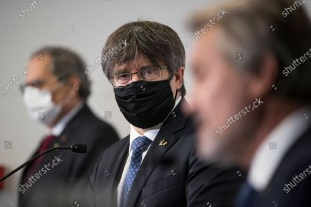 Catalonia's former regional president Carles Puigdemont looks towards Artur Mas during a press conference in Perpignan, southern France, . Carles Puigdemont, Artur Mas, and Quim Torra, three former separatist-minded presidents of Spain's Catalonia region, hold a press conference in Perpignan, France, to denounce what they consider their unfair treatment by Spanish authorities