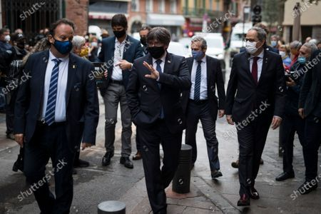 Carles Puigdemont, center, gestures to supporters as he and Quim Torra, right, arrive in Perpignan, southern France, . Carles Puigdemont, Artur Mas, and Quim Torra, three former separatist-minded presidents of Spain's Catalonia region, hold a press conference in Perpignan, France, to denounce what they consider their unfair treatment by Spanish authorities