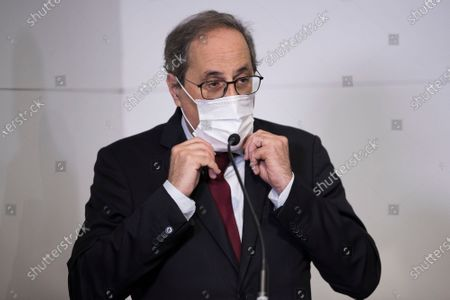 Quim Torra adjusts his face mask during a press conference in Perpignan, southern France, . Carles Puigdemont, Artur Mas, and Quim Torra, three former separatist-minded presidents of Spain's Catalonia region, hold a press conference in Perpignan, France, to denounce what they consider their unfair treatment by Spanish authorities