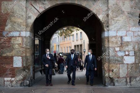Quim Torra, left, Carles Puigdemont, center, and Artur Mas walk towards photographers in Perpignan, southern France, . Carles Puigdemont, Artur Mas, and Quim Torra, three former separatist-minded presidents of Spain's Catalonia region, hold a press conference in Perpignan, France, to denounce what they consider their unfair treatment by Spanish authorities