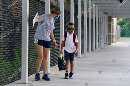 Volunteer Jennifer Smith, left, escorts first grader Zachary Etienne to a classroom on the first day of school at Fox Trail Elementary School, in Davie, Fla. Broward County, Florida schools phased reopening for face-to-face eLearning