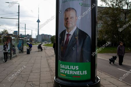 Local resident walk by an election poster showing The Lithuanian Farmers and Greens Union (LVZS) leader, Lithuania's prime minister Saulius Skvernelis in Vilnius, Lithuania, . Lithuanians are voting in the first round of a parliamentary election on Sunday