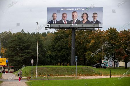 Woman with dog walks by an election poster showing The Lithuanian Farmers and Greens Union (LVZS) leader, Lithuania's prime minister Saulius Skvernelis, center, and other Union members in Vilnius, Lithuania, . Lithuanians are voting in the first round of a parliamentary election on Sunday