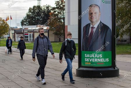 Stock Image of Local residents walk by an election poster showing The Lithuanian Farmers and Greens Union (LVZS) leader, Lithuania's prime minister Saulius Skvernelis in Vilnius, Lithuania, . Lithuanians are voting in the first round of a parliamentary election on Sunday