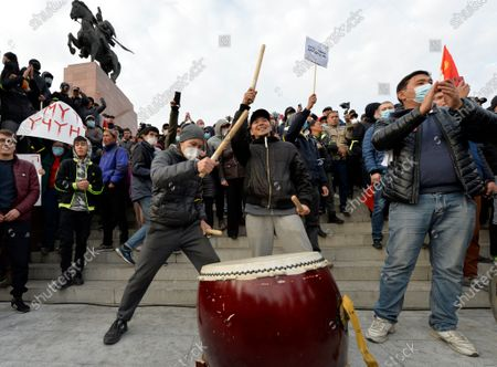 Supporters of former President Almazbek Atambayev bang on the drum during a rally on the central square in Bishkek, Kyrgyzstan, . Sooronbai Jeenbekov, the embattled president of Kyrgyzstan, has moved to end the political turmoil that followed a disputed parliamentary election, ordering a state of emergency in the capital. Jeenbekov has faced calls to resign by protesters who stormed government buildings after Sunday's parliamentary vote was reportedly swept by pro-government parties. Protesters freed former President Almazbek Atambayev, who was jailed on charges seen by his supporters as a political vendetta