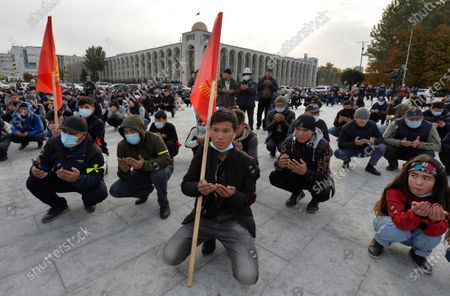 People pray during a rally on the central square in Bishkek, Kyrgyzstan, Sooronbai Jeenbekov, the embattled president of Kyrgyzstan, has moved to end the political turmoil that followed a disputed parliamentary election, ordering a state of emergency in the capital. Jeenbekov has faced calls to resign by protesters who stormed government buildings after Sunday's parliamentary vote was reportedly swept by pro-government parties. Protesters freed former President Almazbek Atambayev, who was jailed on charges seen by his supporters as a political vendetta
