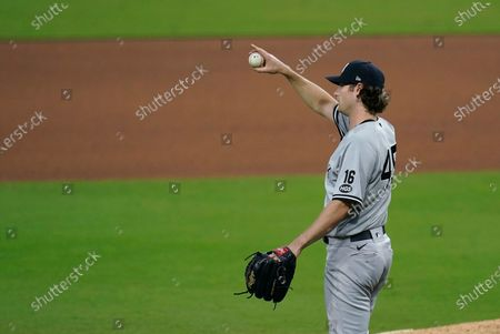 New York Yankees starting pitcher Gerrit Cole points toward Brett Gardner after Gardner made a catch on a ball hit by Tampa Bay Rays' Randy Arozarena during the sixth inning in Game 5 of a baseball AL Division Series, in San Diego