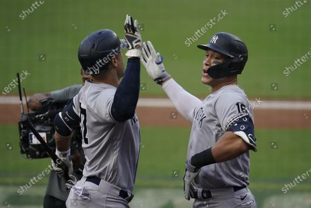 New York Yankees' Aaron Judge, right, celebrates after hitting a solo home run with Giancarlo Stanton during the fourth inning in Game 5 of a baseball American League Division Series against the Tampa Bay Rays, in San Diego