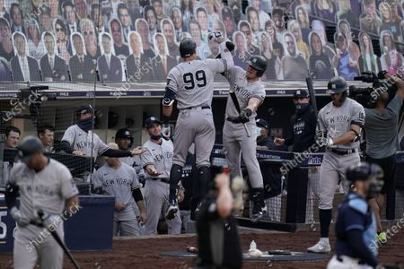 New York Yankees' Aaron Judge (99) and Luke Voit celebrate a solo home run by Judge during the fourth inning in Game 5 of a baseball American League Division Series against the Tampa Bay Rays, in San Diego