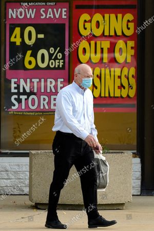 Stock Picture of Shopper wears a face mask as he leaves a Lord & Taylor department store in Northbrook, Ill., . The coronavirus pandemic has not been good for Lord & Taylor as it announced its bankruptcy and is going out of business