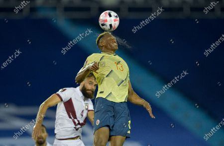 Colombia's Yerry Mina, right, and Venezuela's Jhon Chancellor go for a header during a qualifying soccer match for the FIFA World Cup Qatar 2022 in Barranquilla, Colombia
