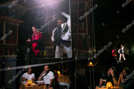 """Flamenco dancers Marina Perez and del Pozo perform behind screens during a flamenco show at the Torres Bermejas """"tablao,"""" or live flamenco venue, in Madrid, Spain, . The passion and drama of live flamenco shows are back on stage in Madrid. But now the performers are behind Perspex screens, keeping their distance from the audience. The tablao has reopened its doors to customers after seven months closed due to the COVID-19 pandemic"""