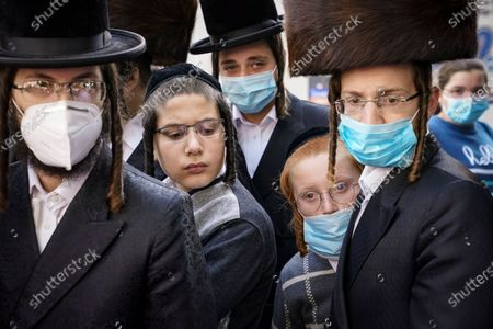 Members of the Orthodox Jewish community gather around a journalist as he conducts an interview on a street corner, in the Borough Park neighborhood of the Brooklyn borough of New York. Gov. Andrew Cuomo moved to reinstate restrictions on businesses, houses of worship and schools in and near areas where coronavirus cases are spiking. Many neighborhoods that stand to be affected are home to large enclaves of Orthodox Jews