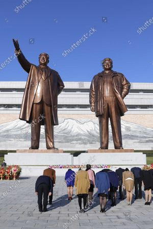 Stock Picture of People vow to the bronze statues of former North Korean leaders Kim Il Sung and Kim Jong Il as they visit the Mansu Hill to lay flowers in Pyongyang, North Korea, on the occasion of the 75th founding anniversary of the country's Workers' Party
