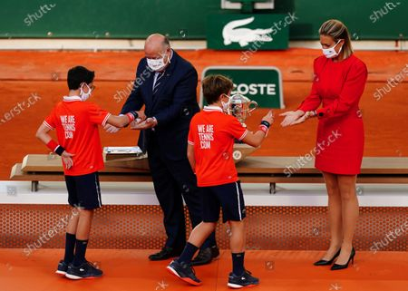 Mary Pierce and Bernard Giudicelli, President of the French Tennis Federation, theatrically have their hands sanitised by ball boys ahead of the trophy presentation