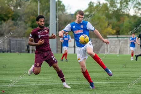 Jamie Todd (#4) of Cowdenbeath FC clears the ball ahead of Jordan Roberts (#11) of Heart of Midlothian FC during the Betfred Scottish League Cup match between Cowdenbeath FC and Heart of Midlothian FC at Bayview Stadium, Methil