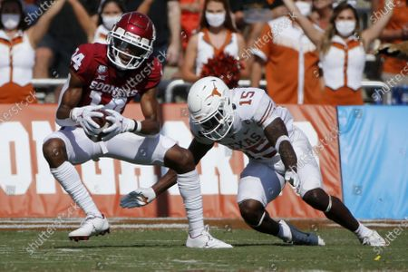 Oklahoma wide receiver Charleston Rambo (14) catches a pass in front of Texas defensive back Chris Brown (15) during an NCAA college football game in Dallas
