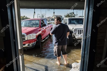 Stock Picture of Bar owner Joey Douget walks out of his business to inspect the flood waters after Hurricane Delta passed over Delcambre, Louisiana, USA on 10 October 2020.  Hurricane Delta made landfall in Louisiana last night, bringing flooding, wind damage and power outages across parts of the state.