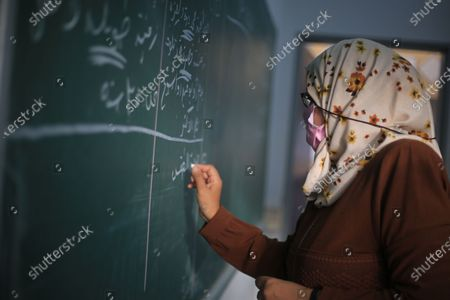A Palestinian teacher wears a protective face mask, teaching in class in Gaza City, after the partial re-opening of schools, amid the coronavirus outbreak.