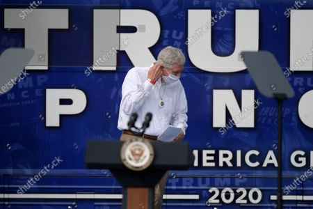 Rep. Daniel Webster, R-Fla., removes his mask before addressing supporters and introducing Vice President Mike Pence during a campaign rally, in The Villages, Fla