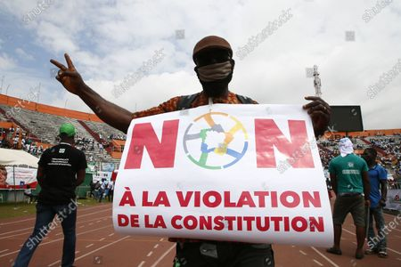 A man holds a sign reading 'No to the violation of the constitution' during a meeting of the Ivorian opposition against the candidacy for re-election of outgoing President Alassane Ouattara. at the Felix Houphouet-Boigny stadium in Abidjan, Ivory Coast, 10 October 2020. Presidential elections in Cote d'Ivoire will take place on October 31, 2020.