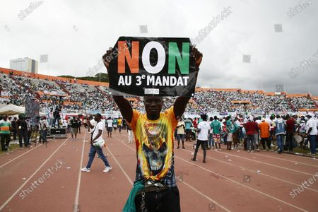 A man holds a sign reading 'No to the 3rd term' as supporters demonstrate during a meeting of the Ivorian opposition against the candidacy for re-election of outgoing President Alassane Ouattara. at the Felix Houphouet-Boigny stadium in Abidjan, Ivory Coast, 10 October 2020. Presidential elections in Cote d'Ivoire will take place on October 31, 2020.