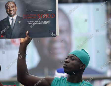 A man holds a poster of the former president of the national assembly Guillaume Soro during a meeting of the Ivorian opposition against the candidacy for re-election of outgoing President Alassane Ouattara. at the Felix Houphouet-Boigny stadium in Abidjan, Ivory Coast, 10 October 2020. Presidential elections in Cote d'Ivoire will take place on October 31, 2020.