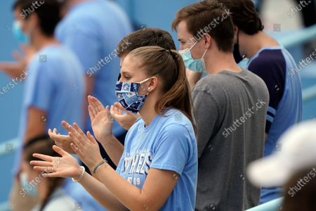 North Carolina fans wear masks while socially distancing during the second half of an NCAA college football game between North Carolina and Virginia Tech in Chapel Hill, N.C