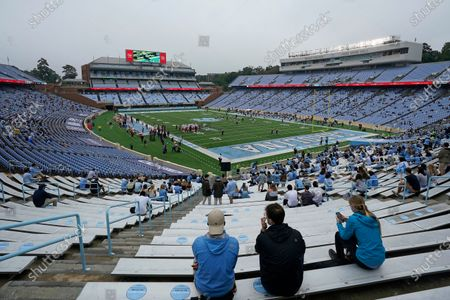 Fans sit social distanced during limited access during the first half of an NCAA college football game between North Carolina and Virginia Tech in Chapel Hill, N.C