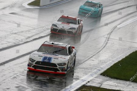 L-R) Chase Briscoe, Brandon Jones and Gray Gauilding compete in the rain during a NASCAR Xfinity Series auto race at Charlotte Motor Speedway in Concord, N.C