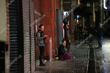 A homeless man sits next to the statue of Cilla Black in Liverpool on Saturday night.