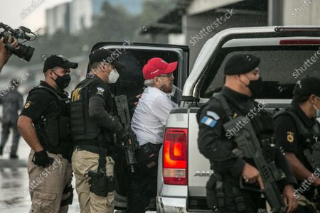 Stock Image of Former guerrilla commander of the Rebel Armed Forces (FAR) of Guatemala, Julio Cesar Macias (C), enters a vehicle, guarded by authorities, after being captured by Interpol, in Guatemala City, Guatemala, 10 October 2020. Julio Cesar Macias Lopez, alias Cesar Montes, was extradited to Guatemala by Mexico to face charges of murder.