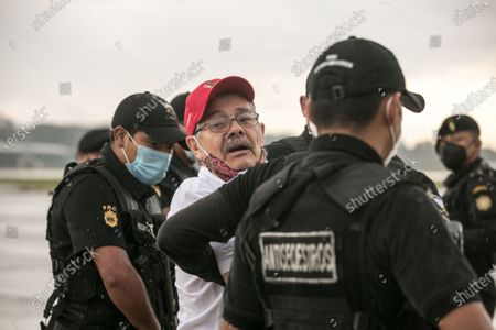 Stock Photo of Former guerrilla commander of the Rebel Armed Forces (FAR) of Guatemala, Julio Cesar Macias (C), is escorted by authorities, after being captured by Interpol, in Guatemala City, Guatemala, 10 October 2020. Julio Cesar Macias Lopez, alias Cesar Montes, was extradited to Guatemala by Mexico to face charges of murder.