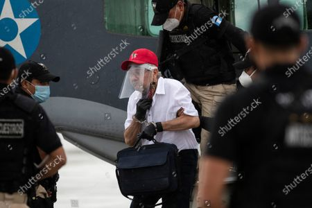 Stock Picture of Police officers escort former leftist rebel Julio Cesar Macias Lopez upon his arrival to the Air Force base in Guatemala City, . Macias Lopez, was arrested in Mexico and deported to Guatemala where he is accused by the Attorney General's office of murdering three soldiers in 2019