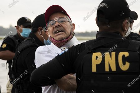 Police officers escort former leftist rebel Julio Cesar Macias Lopez upon his arrival to the Air Force base in Guatemala City, . Macias Lopez, was arrested in Mexico and deported to Guatemala where he is accused by the Attorney General's office of murdering three soldiers in 2019