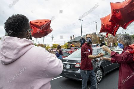 """Cheryl Best (R), an organizer for the event, and her son, Michael Best (M),both wearing facemasks hand out balloons to participants in the """"Safely Supporting Black Lives Matter Car Parade"""", so the cars in the parade can more easily follow one another.  Desmond Fernandez in association with Worthington Racial Justice Organizing, 8 Minutes and 46 Seconds to Justice and Cheryl Best, a 72 year old activist, put together """"Safely Supporting Black Lives Matter Car Parade"""". The BLM (Black Lives Matter) Car Parade met in the parking lot of Broad St. Presbyterian Church where they decorated their cars with BLM words, names of people killed in by the justice system and balloons to indicate parade participants. Best said, """"...I couldn't participate in the protests because of my age,"""" so she put together this socially distanced car parade routed past different buildings involved in the justice system."""