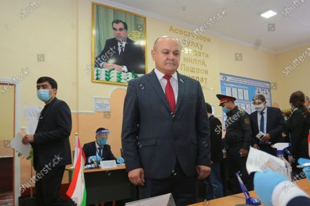 Presidential candidate of Agrarian Party Rustam Latifzoda receives his ballot at a polling station during the presidential election with a portrait of Tajik President Emomali Rahmon in the background in Dushanbe, Tajikistan, . Tajik President Emomali Rakhmon, who has run the ex-Soviet nation bordering Afghanistan for more than a quarter-century, is set to win another seven-year term in office