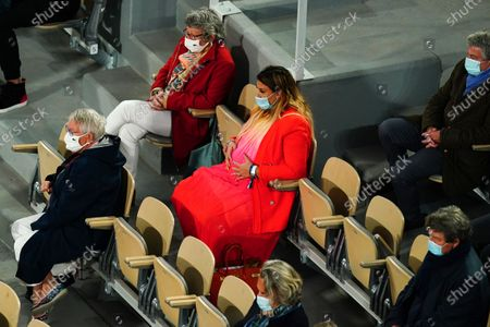 A pregnant Marion Bartoli holding her tummy watching the Men's Singles final
