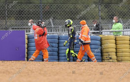 Italian rider Valentino Rossi of the Monster Energy Yamaha MotoGP, centre, walks after falling down during the MotoGP race of the French Motorcycle Grand Prix at the Le Mans racetrack, in Le Mans, France