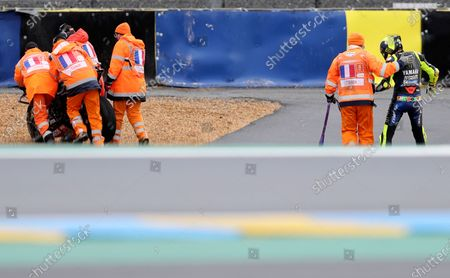 Italian rider Valentino Rossi of the Monster Energy Yamaha MotoGP, right, walks after falling down during the MotoGP race of the French Motorcycle Grand Prix at the Le Mans racetrack, in Le Mans, France