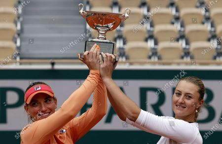 Kristina Mladenovic of France (R) and Timea Babos of Hungary posing with their trophy after winning against Alexa Guarachi of Chile and Desirae Krawczyk of the USA in their women's doubles final match during the French Open tennis tournament at Roland Garros in Paris, France, 11 October 2020.
