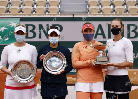 Kristina Mladenovic of France (R) and Timea Babos of Hungary (2R) posing with their trophy after winning against Alexa Guarachi of Chile (L) and Desirae Krawczyk of the USA (holding their runner-up trophy) in their women's doubles final match during the French Open tennis tournament at Roland Garros in Paris, France, 11 October 2020.