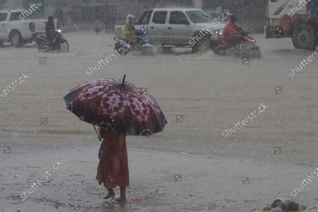 Small girl holds an umbrella as she walks along a flooded main road during the heavy raining on the outskirts of Phnom Penh, Cambodia, . Flooding in Cambodia has killed at least 11 people since the beginning of the month, a disaster official said Sunday