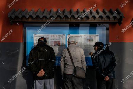 Elder men gather to read newspapers at Beihai Park amid coronavirus pandemic in Beijing, China, 11 October 2020.