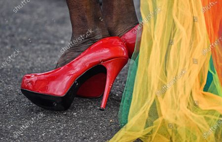 The red high heels of a participants of the Cologne Pride rally are pictured in Cologne, Germany, . This year's Christopher Street Day (CSD) Gay Parade takes place as a demonstration for LGBTQ rights with social distancing on bicycles trough the city, followed by a limited rally due to the coronavirus pandemic